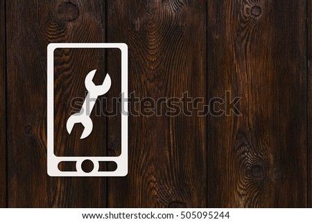 Paper mobile phone or smartphone with wrench sign inside. Repair concept. Abstract conceptual image. Dark wooden background