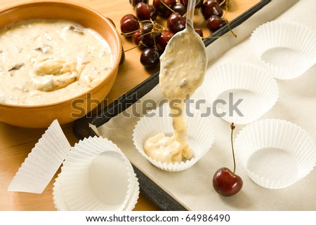 Paper muffin cases being filled with dough for cherry chocolate muffins - stock photo