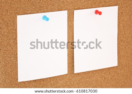 Paper nailed to a corkboard