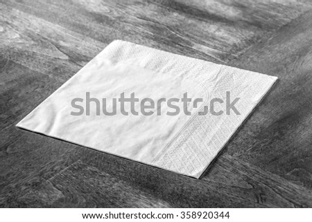 Paper napkin on wooden table - stock photo