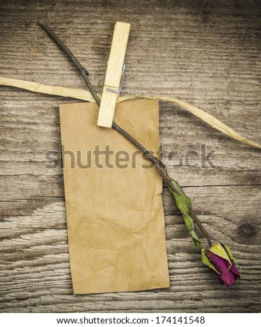 Paper note with dried rose on a old wooden boards - stock photo