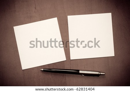 Paper note with pen on wooden background - stock photo
