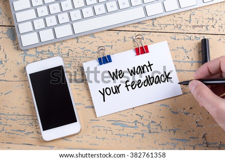 Paper note with text We want your feedback - stock photo