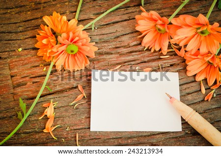 Paper, notebooks, pens with orange flowers on the table, vintage retro style. - stock photo