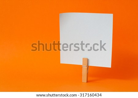 paper notes and clothespins isolated on orange background - stock photo
