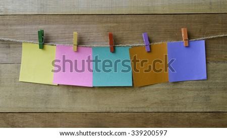 Paper notes hanging on rope, Wooden background