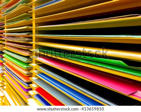 Paper of various colors arranged in racks.