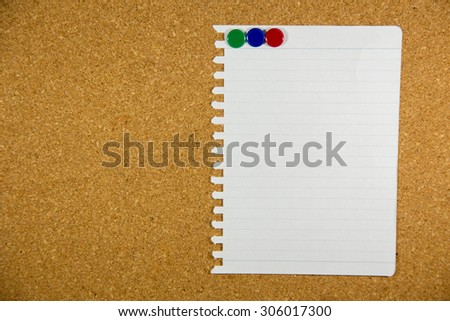 paper on cork board with sticky note pinned