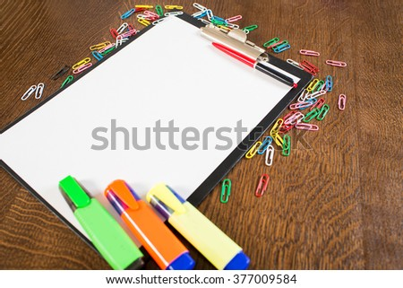 paper on the folder and office supplies on the wooden background
