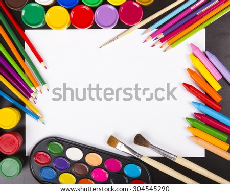 Paper on wooden background with scattered materials for drawing around it - stock photo