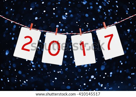 Paper or photo frames  with 2017 figures hanging on the red striped rope. Snowfall background, New year design.