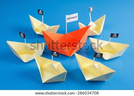Paper origami ship and several pirate Vessel with black flag Jolly Roger - stock photo
