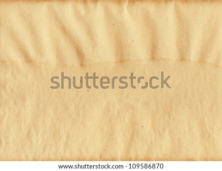 paper packing wet moist with patches of water empty space for the text background brown yellow textured and dark reflections