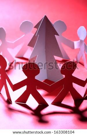 Paper people dancing around Christmas tree - stock photo
