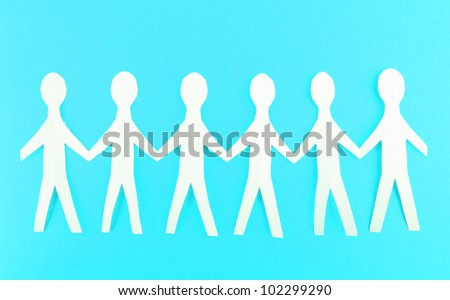Paper people on blue background - stock photo