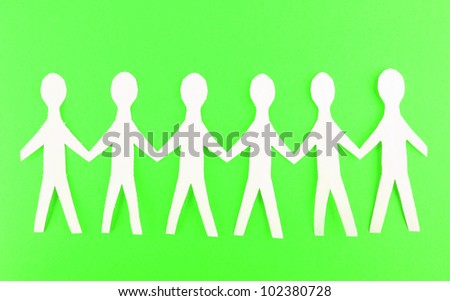 Paper people on green background - stock photo