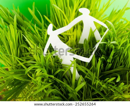Paper people on green grass on bright background  - stock photo
