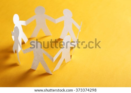 Paper people on the orange paper background - stock photo