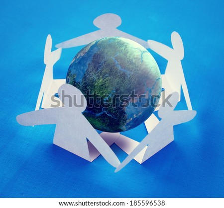 Paper people sitting around the globe holding hands. - stock photo