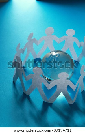 Paper people standing around globe holding hands. - stock photo