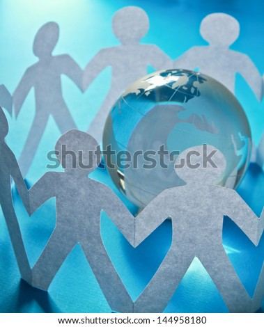 Paper people standing in a circle around glass globe isolated on blue background - stock photo
