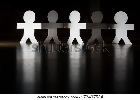 Paper people team group holding hands. - stock photo
