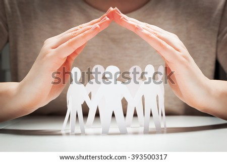 Paper people under hands in gesture of protection. Concept of insurance, social protection and support.