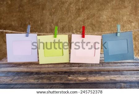 Paper photo frame on clothesline on grunge background, Valentine concept - stock photo
