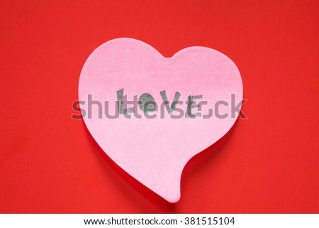 paper pink heart on red background - stock photo