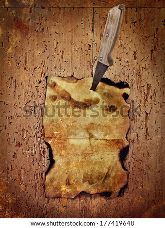 Paper pinned with a knife to the old wooden wall - stock photo