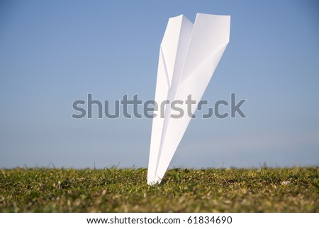 Paper plane crashed into the ground - stock photo