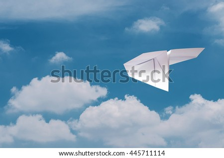 Paper plane flying over clouds with blue sky.