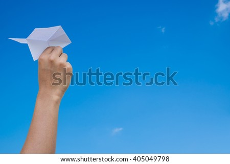 paper plane in a businessman hand on blue skies background - stock photo
