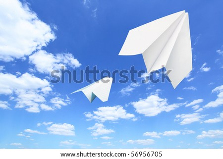 Paper planes flying. Sky and clouds in the background - stock photo