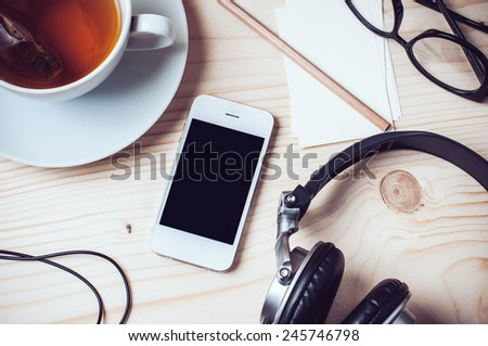 Paper records, cup of tea, mobile phone, headphones, glasses and pencil on wooden office desktop, hipster style - stock photo