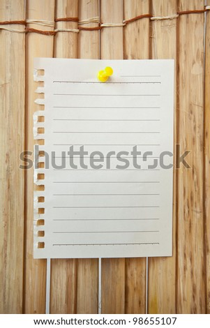 paper sheet and pin on wood texture background