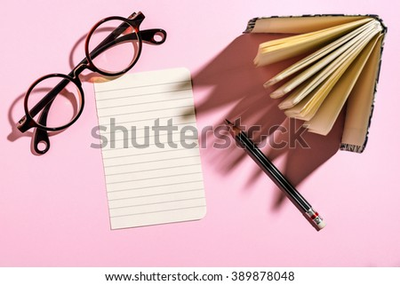 Paper sheet, glasses, notebook and pencil on pink paper board, top view - stock photo
