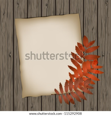 Paper sheet with autumn leaves on wooden background texture. - stock photo