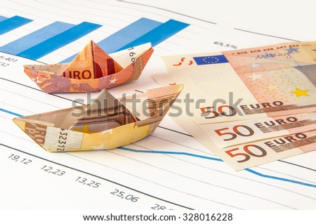 Paper ship carrying money along the finance diagram. - stock photo