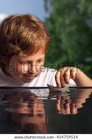 paper ship in children hand - stock photo
