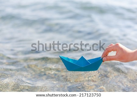 paper ship in hand  - stock photo