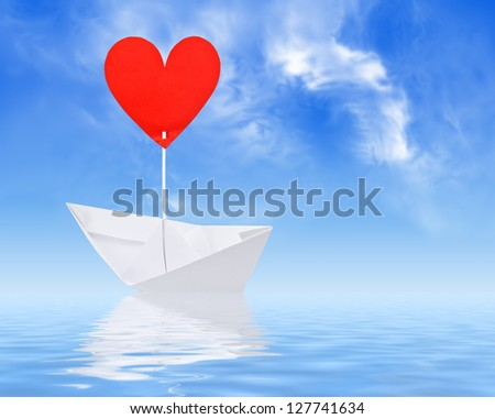 Paper ship with red heart sail on white background - stock photo