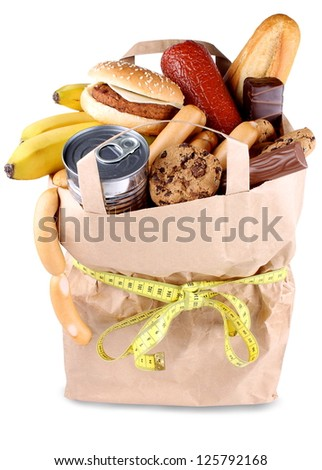 Paper shopping bag with high-calorie foods and measuring tape isolated - stock photo