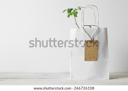 Paper shopping bag with small green plant in it presented on white background. Ecology concept. - stock photo