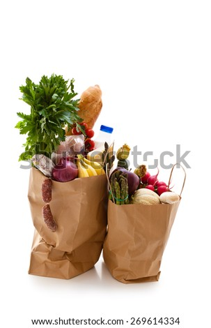 Paper shopping bag with variety of fresh organic vegetables, bread and milk. Isolated on white background. - stock photo