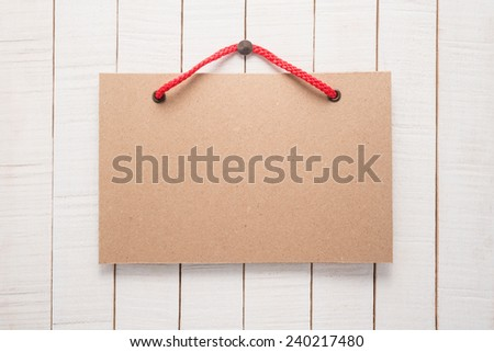 Paper signboard with rope on wooden background   - stock photo