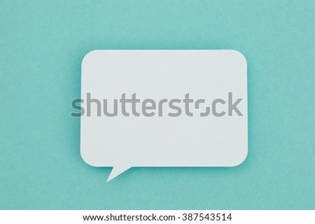 Paper speech bubble on a blue background. Conceptual image about communication and social media. - stock photo