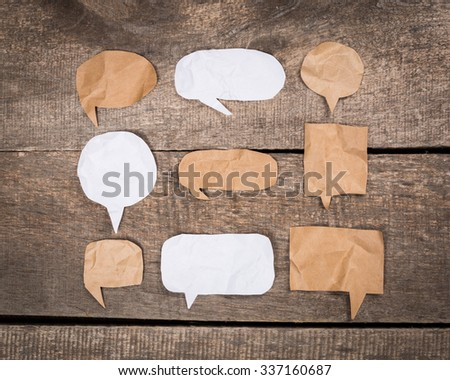 Paper speech bubbles on wooden background