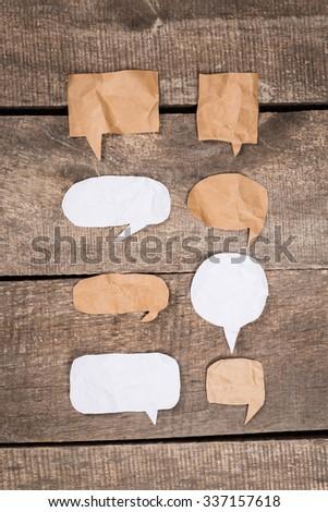 Paper speech bubbles on wooden desk - stock photo