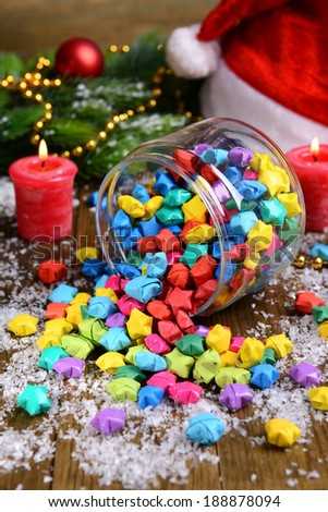 Paper stars with dreams in jar on table on wooden background